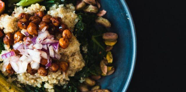 A blue bowl containing a vegan salad with quinoa, kale,pistachios, nectarines
