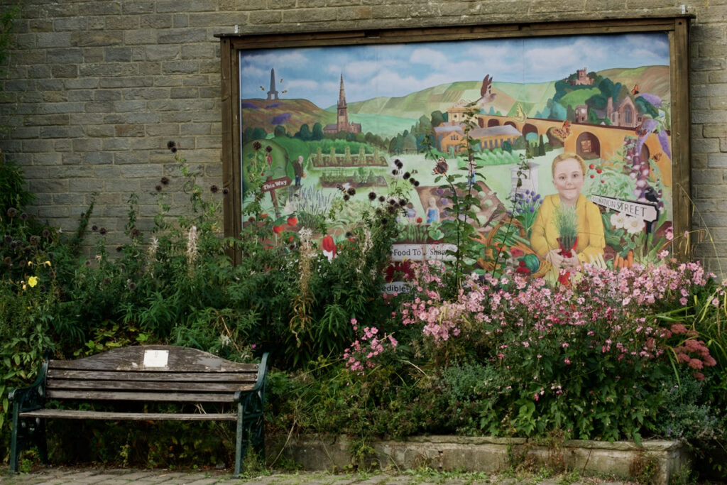 """A photograph of the Incredible Edible mural on the wall of Todmorden Library and facing lock gates on the Rochdale Canal. There are many plants in front of it and a bench for sitting on.  The mural features a girl in front of a scene including the Stoodley Pike monument on a hill near Todmorden, the Unitarian Church, railway arches, a sign for """"Pollination Street"""" - an area of derelict land reclaimed by fruit and vegetable planting and a grassed area for social gatherings and events."""