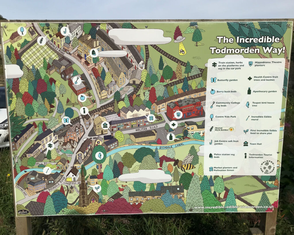 The Incredible Todmorden Way. This is a photograph of a stylised and hand painted map of Todmorden located on a sign board positioned adjacent to an Incredible Edible planting bed and little library on Burnley Road. The map shows Incredible Edible landmarks.