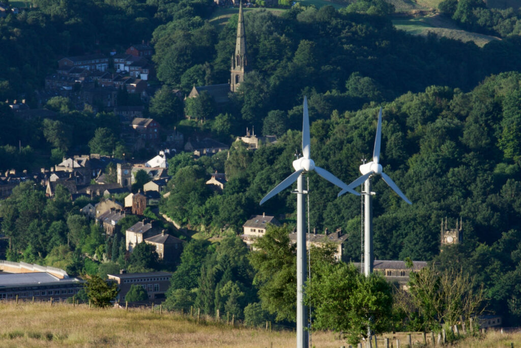A photo of Todmorden viewed from a hillside. The pointed spire visible in the photo is part of the Unitarian Church, the epicentre of Incredible Edible's work. The picture shows houses and other buildings with many green trees around them. In the foreground are two wind turbines.